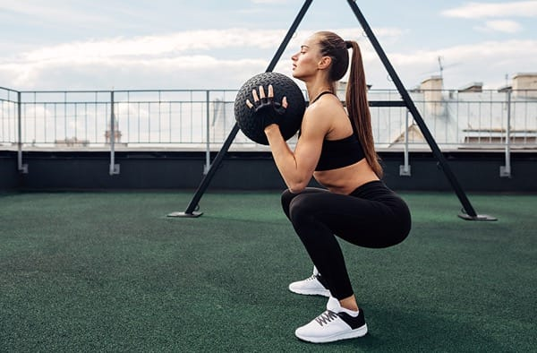 Woman doing squats on astroturfed outdoor area with a medicine ball